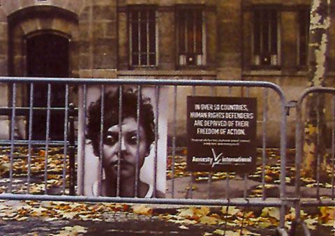 Ad showing a portrait of an individual behind a public fence