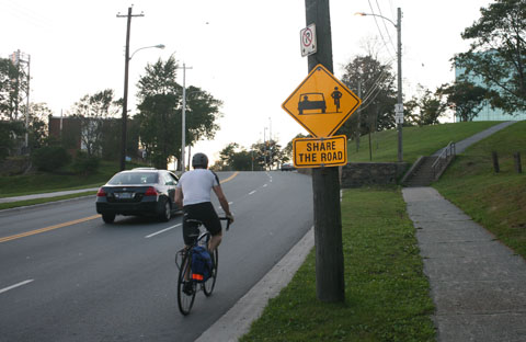 Sign on street promoting drivers and bikers sharing the street