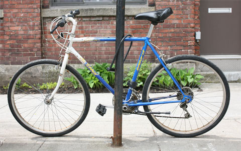 blue and white male bike locked on a pole with house in the background