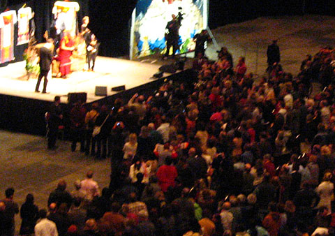 Dalai Lama on stage surrounded by a crowed of people during the conference in Ottawa