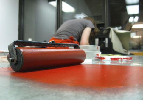 A roller with red color in the foreground, Brigitte working in the back