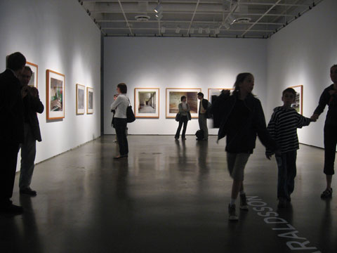 gallery space with visitors looking at photographs on the three walls