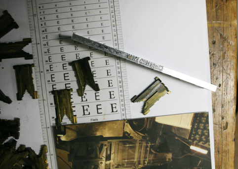 Line of letters made by a linotype machine and other objects on a table
