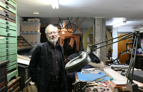 Glenn Goluska in his studio surrounded by cases for letters and an office table