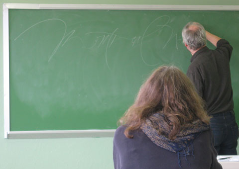 Calligrapher writing on green chalkboard in classroom