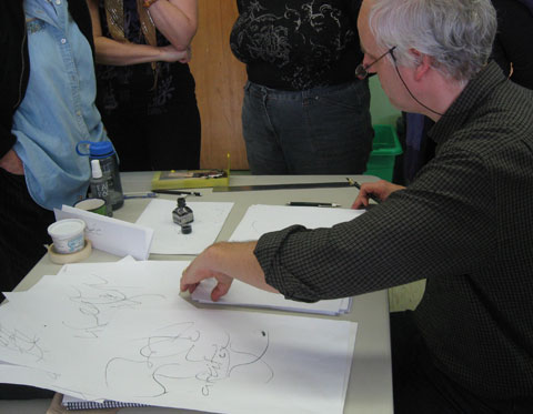Calligrapher demonstrating writing with a pen to a group of people standing around a table