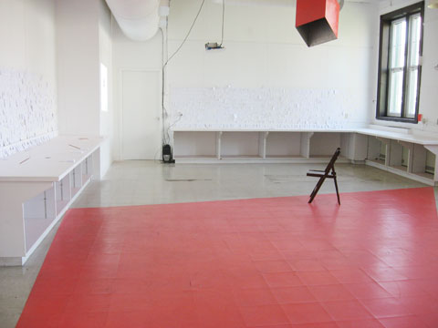 Installation of amuse project featuring small cards on wall in a large space with red parts