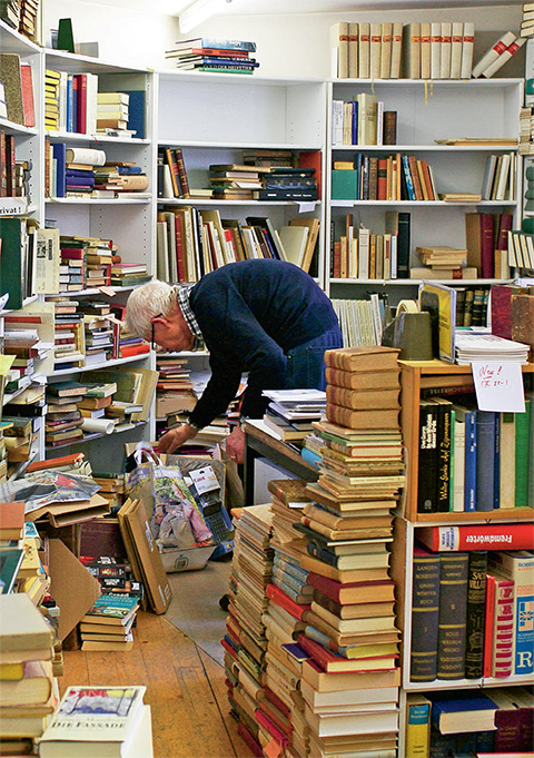 Elderly man surrounded by bookshelves and books