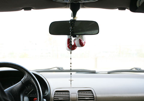 Chaplet and little boxing gloves on the car mirror space
