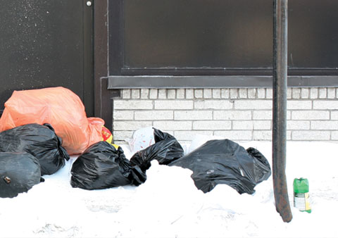 Orange and black Garbage Bags on Boulevard St Laurent, Corner Boulevard St-Joseph E on sidewalk