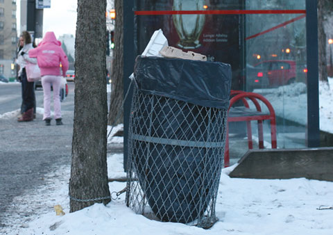 Garbage can on Rue Sherbrooke E, Corner Avenue Emile-Duploye with a busstop and people waiting
