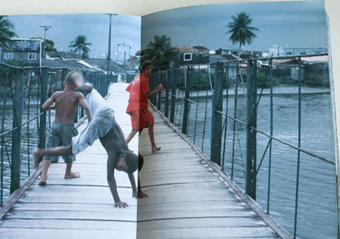 Double-page of the Ilha de Deus Exposition Catalogue with an image of playing boys on a bridge